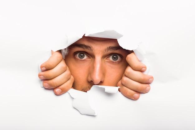 Jeune homme regardant à travers une déchirure de papier Photo Premium