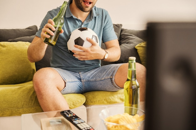 Jeune homme regarde le football à la télévision et boit de la bière à la maison Photo Premium
