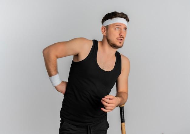 Jeune Homme De Remise En Forme Avec Bandeau Tenant Une Batte De Baseball à Côté Avec Expression De Confusion Debout Sur Fond Blanc Photo gratuit