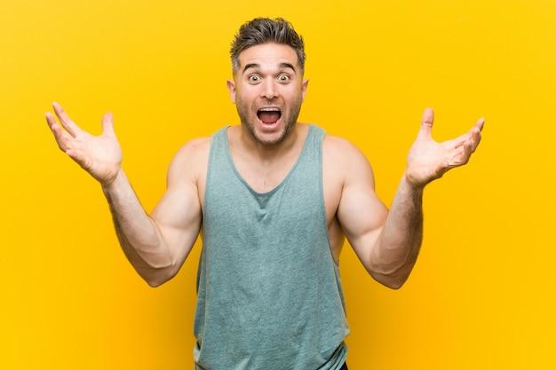 Jeune homme de remise en forme célébrant une victoire ou un succès, il est surpris et choqué Photo Premium