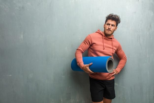 Jeune homme de remise en forme contre un mur grunge doutant et confus, pensant à une idée ou inquiet pour quelque chose. tenant un tapis bleu pour la pratique du yoga. Photo Premium