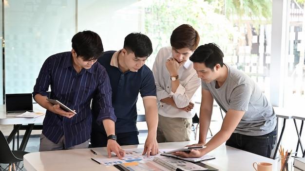 Jeune homme rencontre avec le projet d'entreprise de démarrage sur la table de bureau Photo Premium