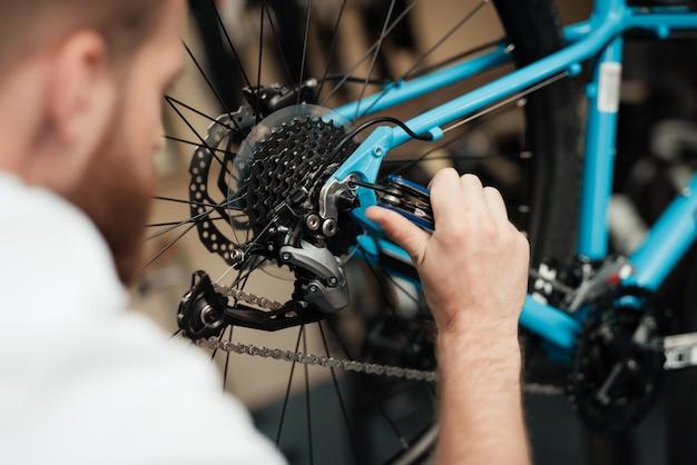 Un jeune homme répare un vélo dans un magasin Photo Premium