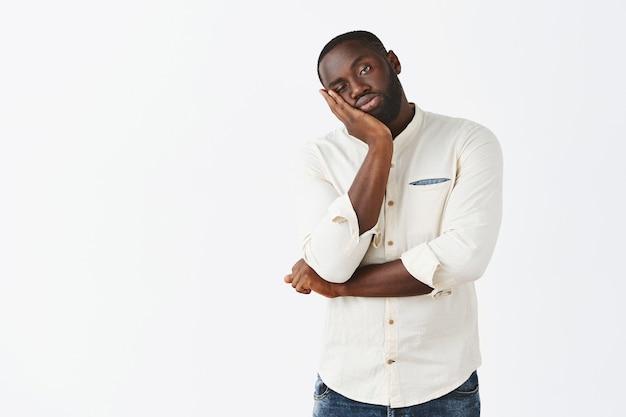 Jeune Homme Réticent Et Ennuyé Posant Contre Le Mur Blanc Photo gratuit