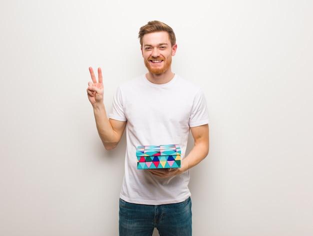 Jeune homme rousse amusant et heureux de faire un geste de victoire. tenir une boîte cadeau. Photo Premium