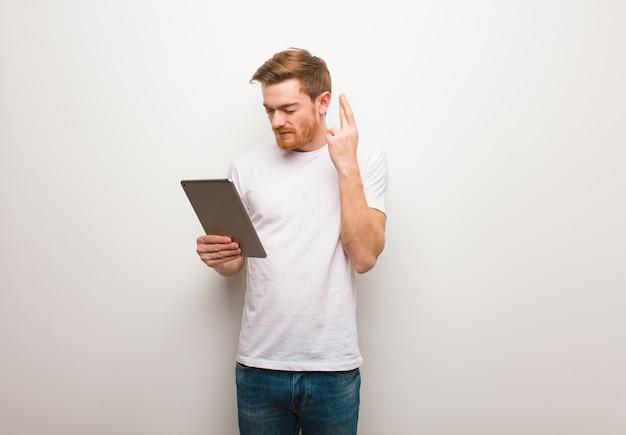 Jeune Homme Rousse Croisant Les Doigts Pour Avoir De La Chance. Tenant Une Tablette. Photo Premium