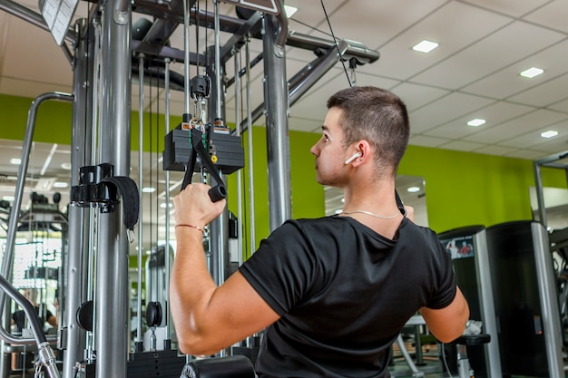 Jeune homme s'entraînant dans la salle de sport Photo gratuit