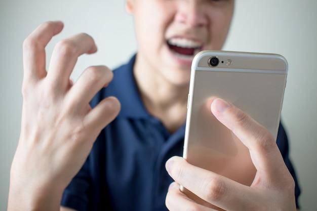 Le jeune homme s'est senti en colère du smartphone avec des problèmes ou des erreurs. Photo Premium