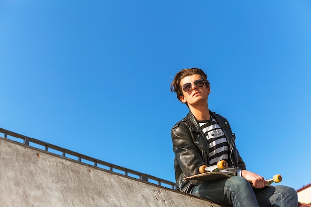 Jeune homme avec sa planche à roulettes dans le skate park Photo gratuit