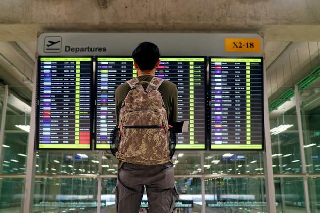 Jeune Homme Avec Sac à Dos En Regardant L'écran D'affichage Des Informations De Vol Flou à L'aéroport Photo Premium
