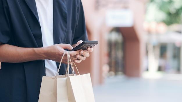 Jeune homme avec des sacs utilise un téléphone portable tout en faisant des achats Photo Premium