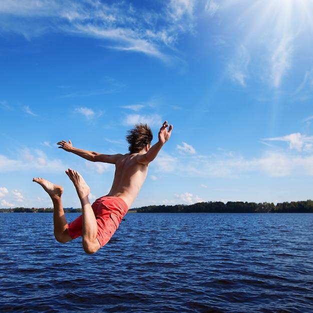 Jeune homme sautant dans l'eau Photo Premium