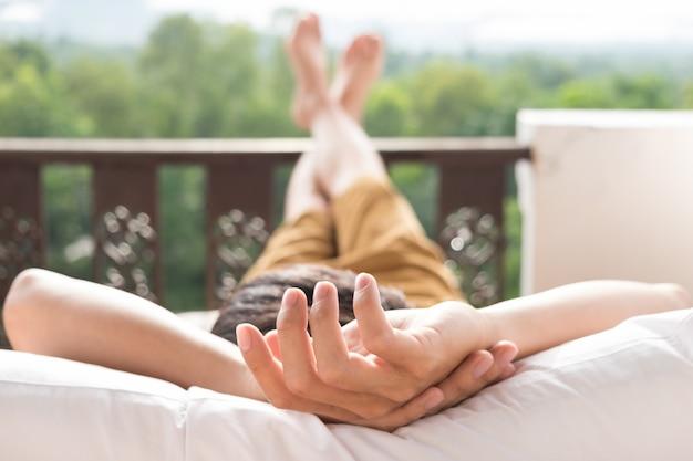 Le jeune homme se détend sur le lit et profite de la vue sur la montagne Photo gratuit