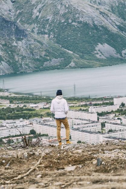 Un jeune homme se dresse sur une montagne et regarde un beau paysage Photo Premium