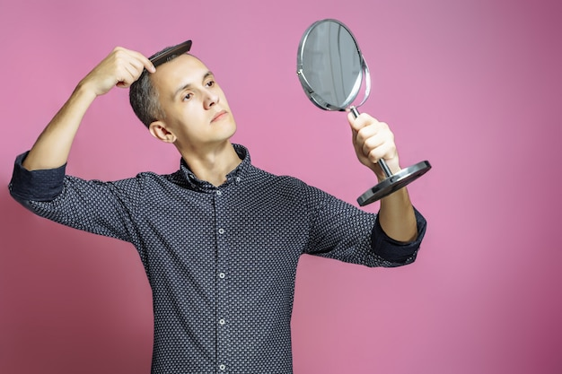 Jeune homme se peignant les cheveux devant un miroir sur fond rose. Photo Premium