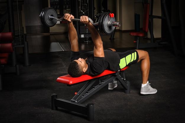 Jeune homme, séance, banc, presse française, séance d'entraînement, dans, gymnase Photo Premium