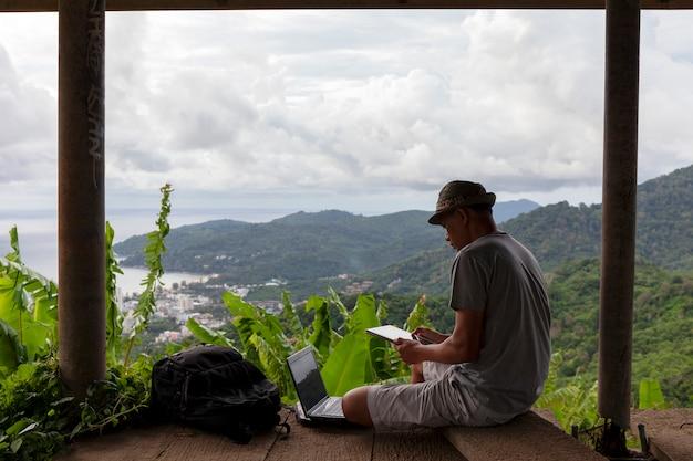 Jeune homme, séance, utilisation, ordinateur portable, contre, paysage, paysage, forêt, et, mer andaman, dans, phuket, thaïlande Photo Premium