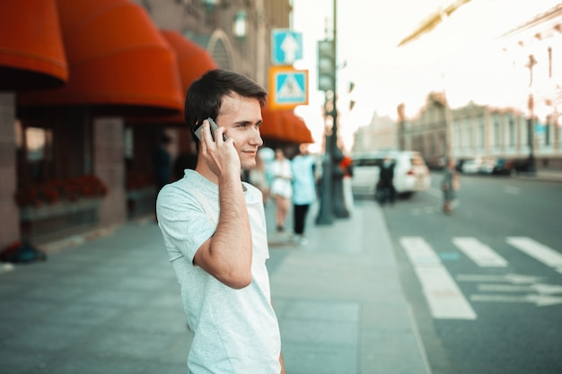 Jeune Homme Séduisant, Marchant Dans La Ville Et à L'aide De Smartphone Photo Premium