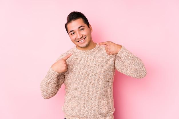 Jeune Homme Sinueux Posant Dans Un Mur Rose Sourit Isolé, Pointant Du Doigt La Bouche. Photo Premium