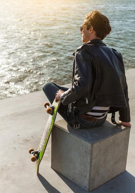 Jeune homme avec un skateboard près de la mer Photo gratuit