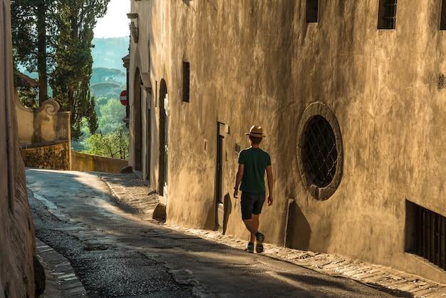 Jeune Homme Solitaire Marchant Le Long De La Rue à Côté D'un Vieux Bâtiment En Béton Photo gratuit