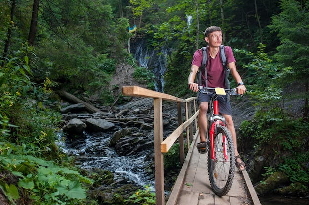 Jeune homme sur son vélo dans la forêt Photo Premium