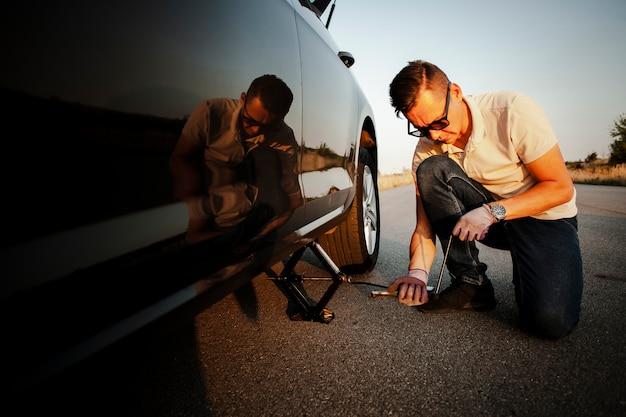 Jeune homme soulevant la voiture avec Photo gratuit