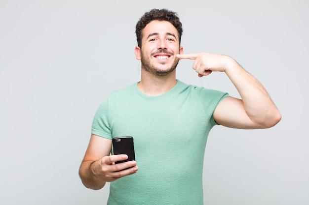 Jeune Homme Souriant Avec Confiance En Montrant Son Large Sourire, Attitude Positive, Détendue Et Satisfaite Photo Premium