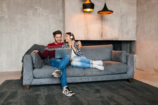 Jeune Homme Souriant Et Femme Assise à La Maison En Hiver à La Recherche D'un Ordinateur Portable Avec Une Expression De Visage Heureux, à L'aide D'internet Photo gratuit