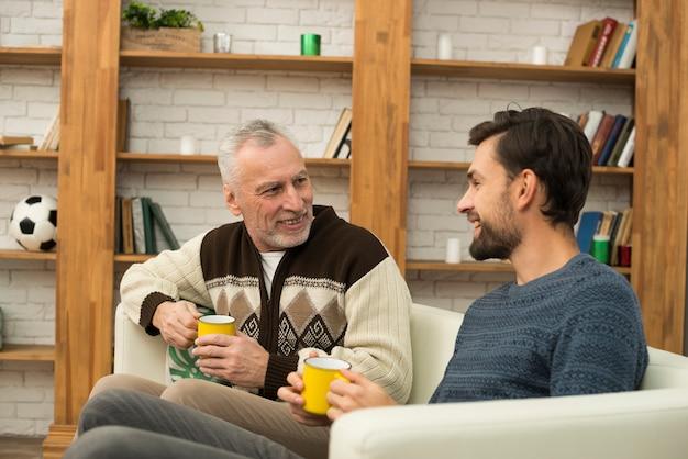 Jeune homme souriant et homme âgé avec des tasses sur le canapé Photo gratuit