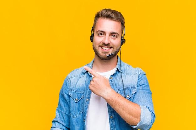 Jeune Homme Souriant Joyeusement, Se Sentant Heureux Et Pointant Vers Le Côté Et Vers Le Haut, Montrant L'objet Dans L'espace De Copie Photo Premium