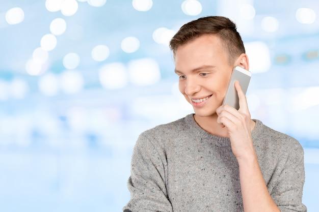 Jeune homme souriant parlant au téléphone Photo Premium