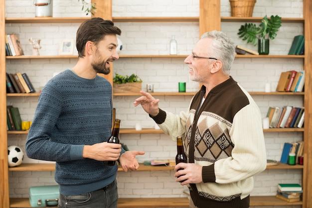 Jeune homme souriant parlant avec un homme âgé avec des bouteilles Photo gratuit