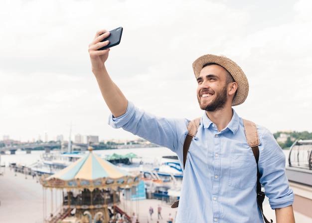 Jeune Homme Souriant Tenant Un Téléphone Cellulaire Et Prenant Selfie à L'extérieur Photo gratuit