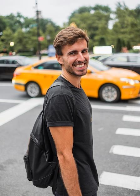 Jeune homme, sourire, près, passage piéton Photo gratuit