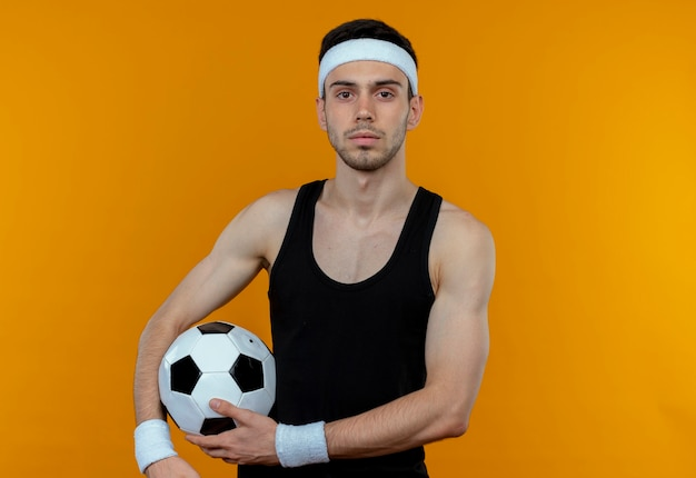 Jeune Homme Sportif En Bandeau Tenant Un Ballon De Football Avec Une Expression Sérieuse Confiante Debout Sur Un Mur Orange Photo gratuit