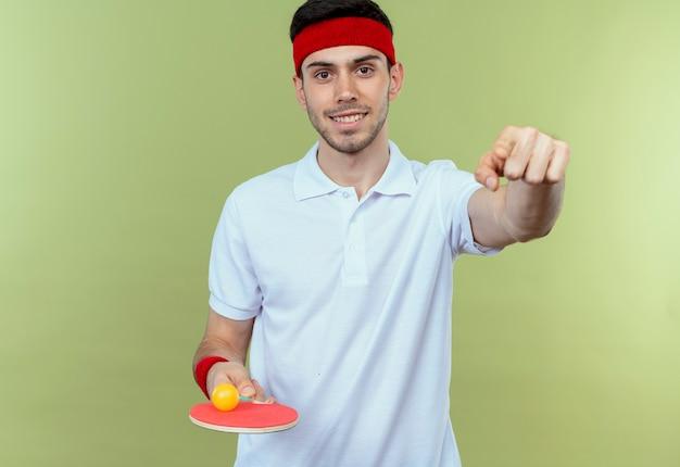 Jeune Homme Sportif En Bandeau Tenant La Raquette Et La Balle Pour Le Tennis De Table Souriant Pointant Avec L'index à Vous Debout Sur Le Mur Vert Photo gratuit