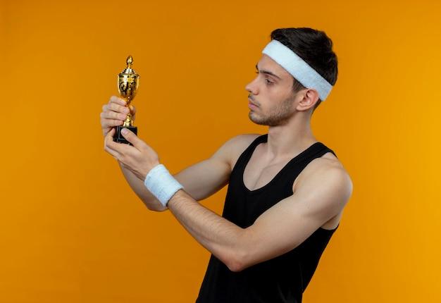 Jeune Homme Sportif En Bandeau Tenant Son Trophée En Le Regardant Avec Une Expression Sérieuse Confiante Debout Sur Un Mur Orange Photo gratuit