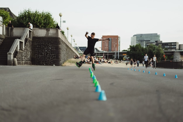 Jeune homme sportif en rollers dans une ville européenne. sports en milieu urbain. Photo gratuit