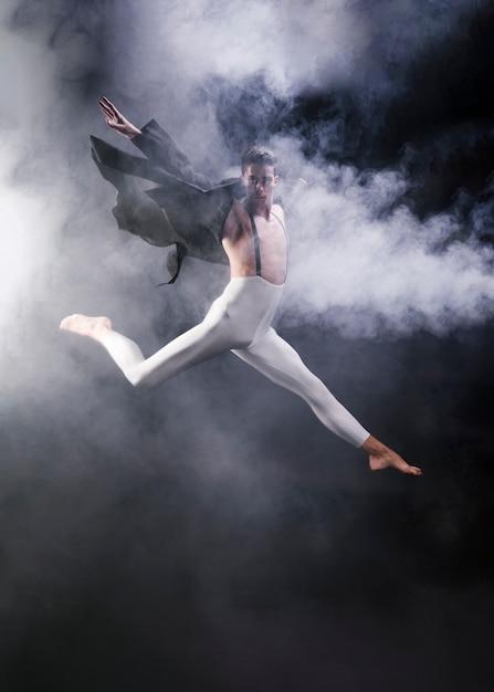 Jeune homme sportif sautant avec les jambes étendues et les mains près de la fumée Photo gratuit