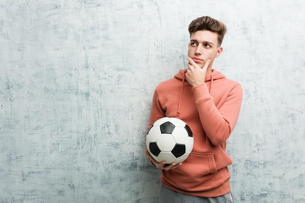 Jeune homme sportif tenant un ballon de football à la recherche de côté avec une expression douteuse et sceptique. Photo Premium