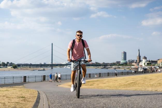 Jeune homme sportif à vélo dans une ville européenne. sports en milieu urbain. Photo gratuit