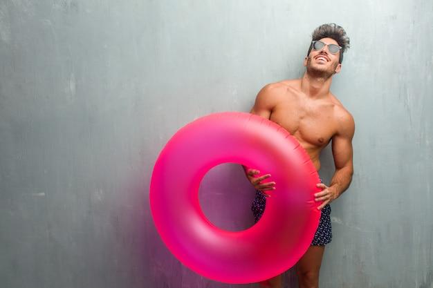 Jeune homme sportif, vêtu d'un maillot de bain contre un mur grunge, riant et s'amusant, détendu et gai, se sentant confiant et ayant du succès Photo Premium