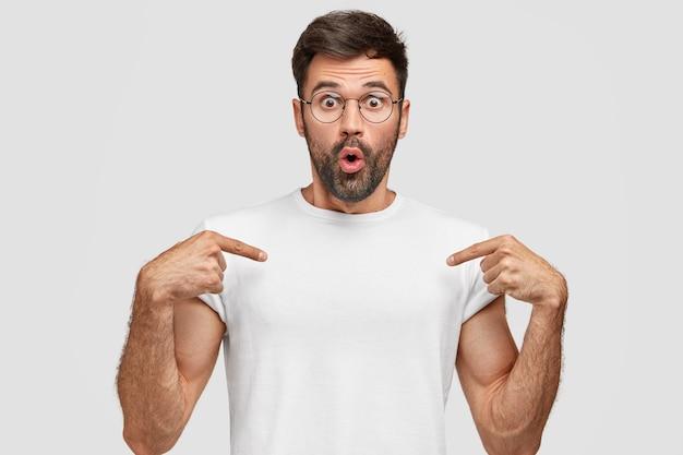Un Jeune Homme Stupéfait Montre Un Espace Vide De T-shirt Photo gratuit