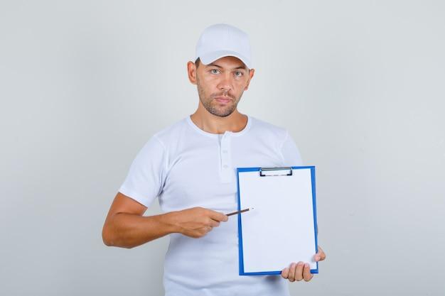 Jeune Homme En T-shirt Blanc Et Casquette Montrant Des Notes Sur Le Presse-papiers Avec Un Crayon, Vue De Face. Photo gratuit