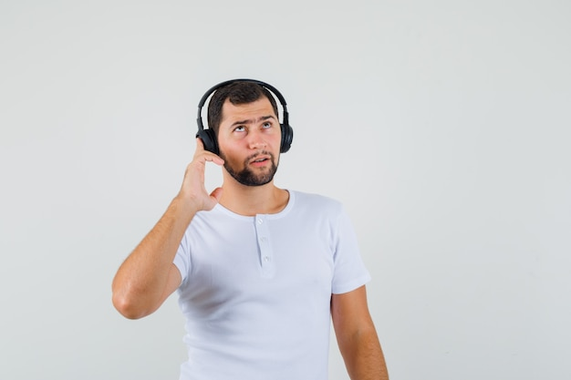 Jeune Homme En T-shirt Blanc, écouter De La Musique Et à La Recherche Concentrée, Vue De Face. Photo gratuit