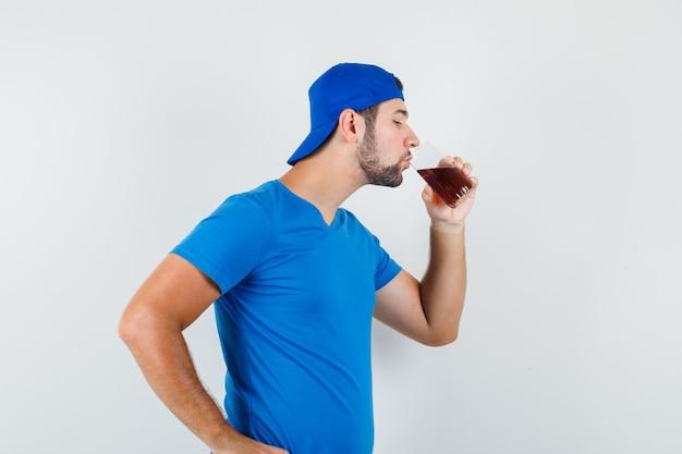 Jeune Homme En T-shirt Bleu Et Casquette De Boire Une Boisson Froide Et à La Soif Photo gratuit