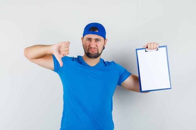 Jeune Homme En T-shirt Bleu Et Casquette Tenant Le Presse-papiers Avec Le Pouce Vers Le Bas Et à La Mécontentement Photo gratuit