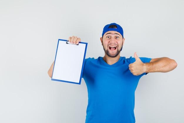 Jeune Homme En T-shirt Bleu Et Casquette Tenant Le Presse-papiers Avec Le Pouce Vers Le Haut Et L'air Heureux Photo gratuit