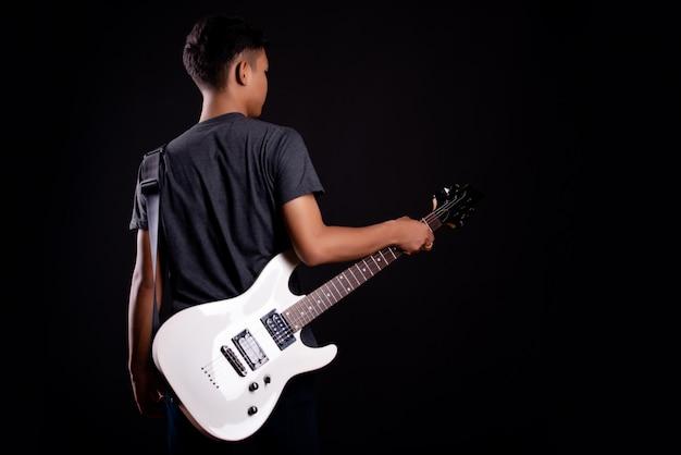 Jeune homme en t-shirt noir avec guitare électrique Photo gratuit